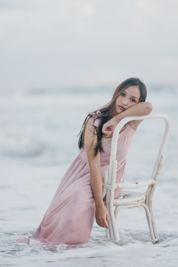 woman wearing pink dress sitting on white chair How to Pose for Amazing Wedding Pictures